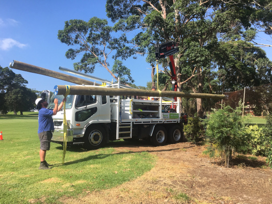 Level 2 Electrician Unloading Timber Power Poles off Truck
